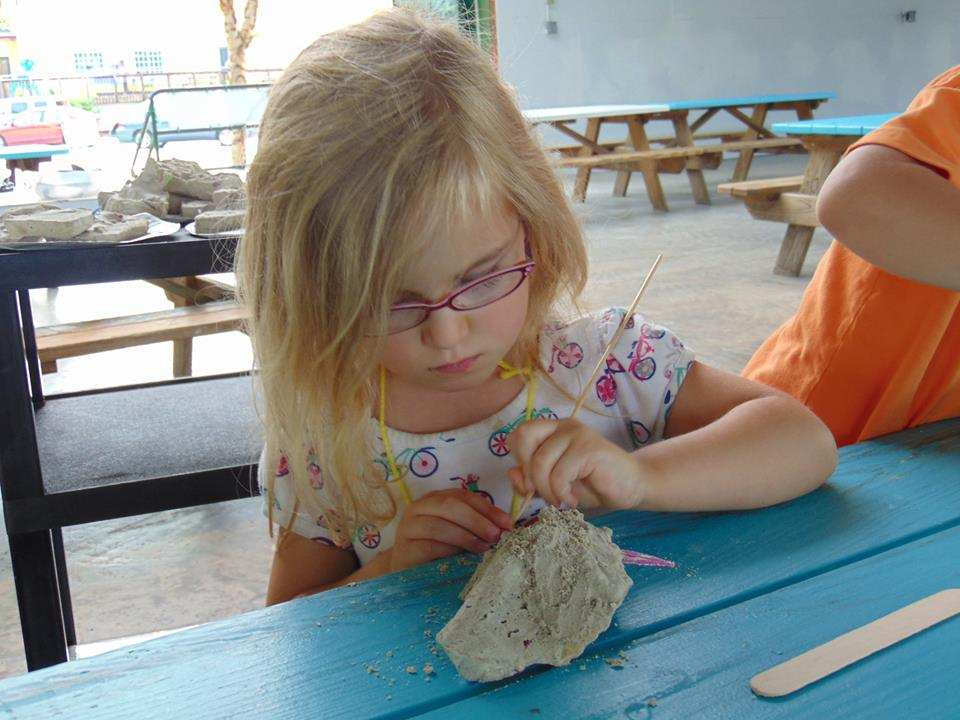 Camper concentrating on uncovering fossil