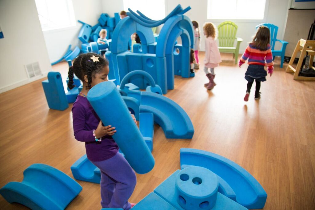Children playing with big blue blocks of Imagination Playground