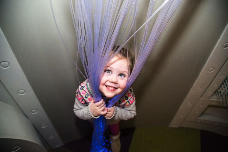 Smiling girl wrapped in color changing fiber optic strands