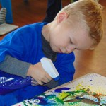 A child uses a spray bottle on his art project