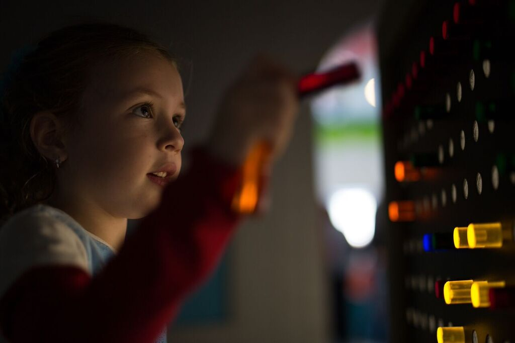 Girl playing with light emitting Reactor Cube in WonderDome