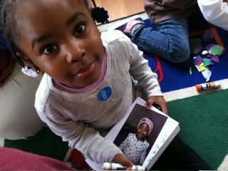 Child holding her photo for art project