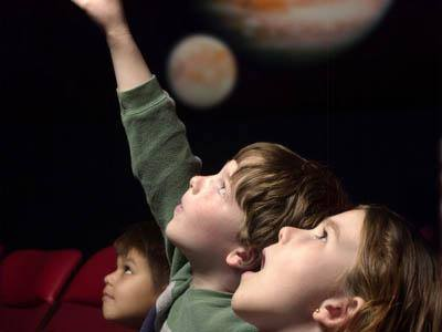 Amazed children looking up in planetarium