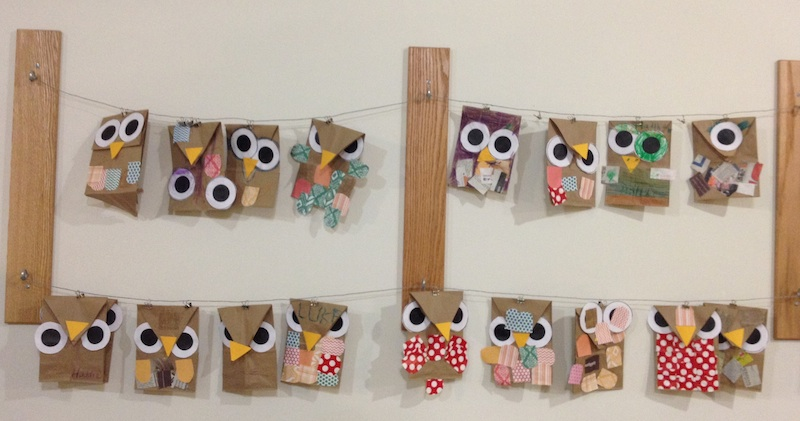 Two rows of hand-crafted owls hang from strings on wall