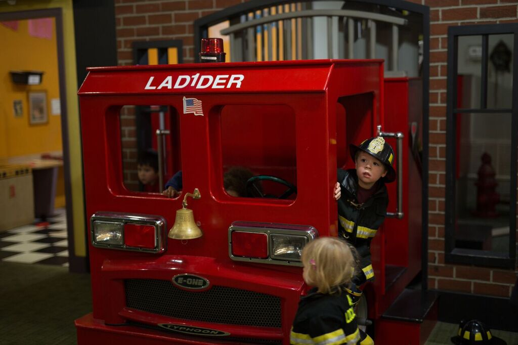 Preschoolers playing on multi-level fire truck exhibit