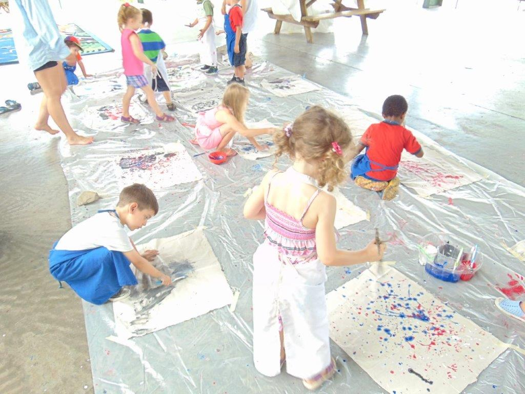 Children painting on paper in the Pavilion