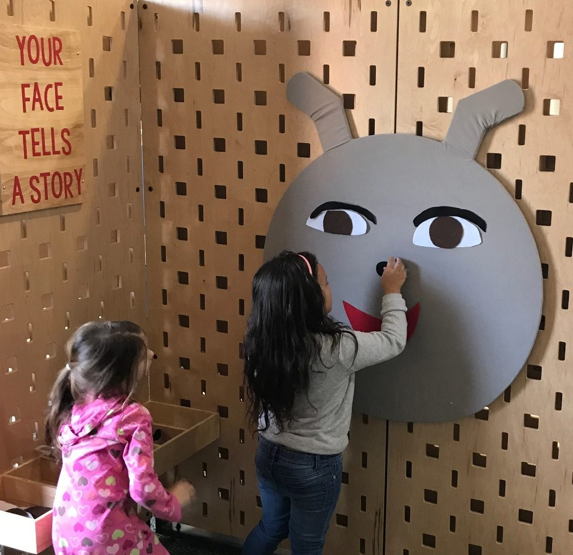 Children creating a giant face with felt shapes