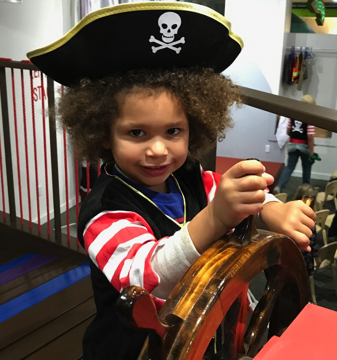 Child in pirate costume at the helm of pirate ship