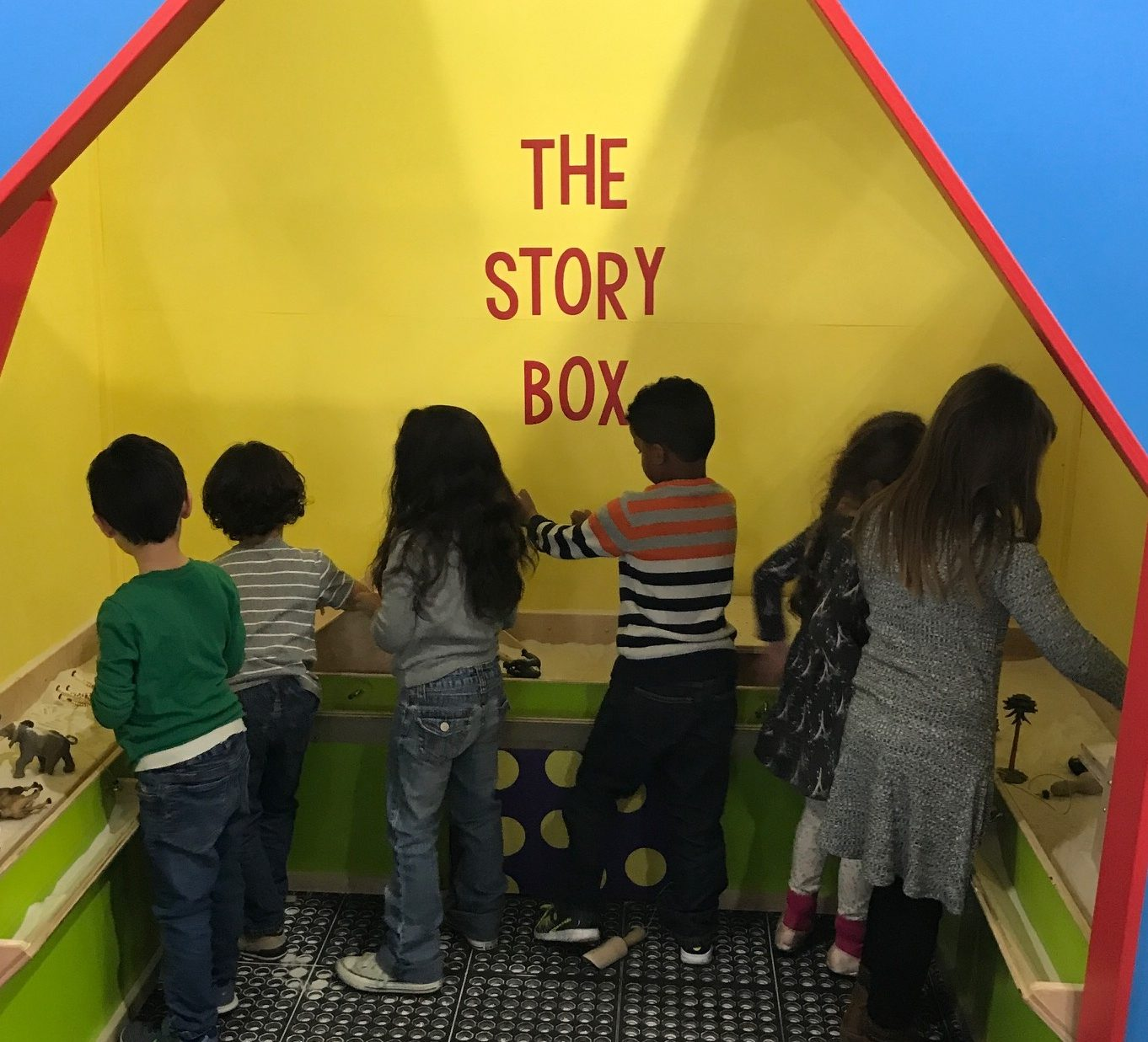 Children playing in the sand at The Story Box exhibit
