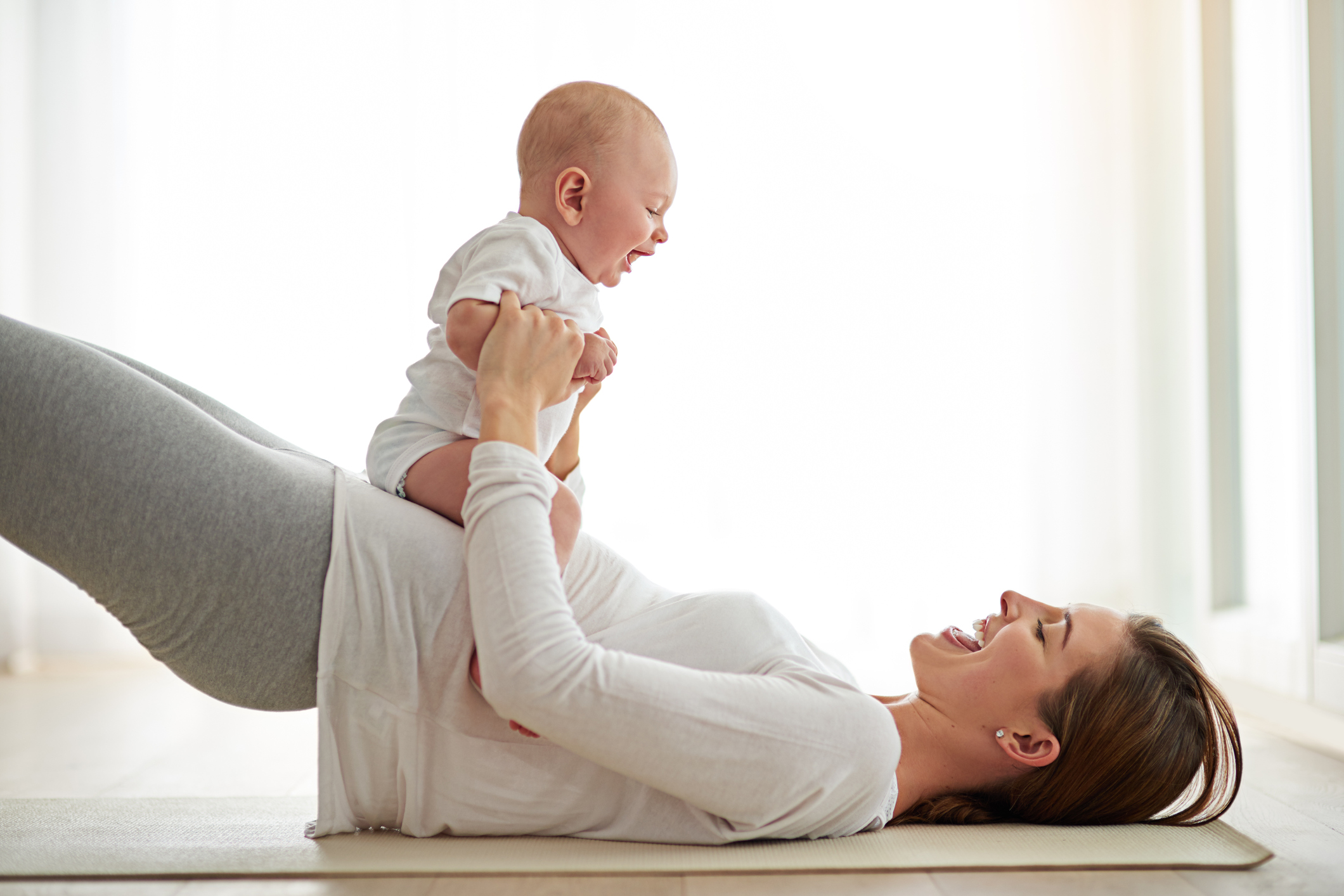 Young woman working out with her baby boy at home