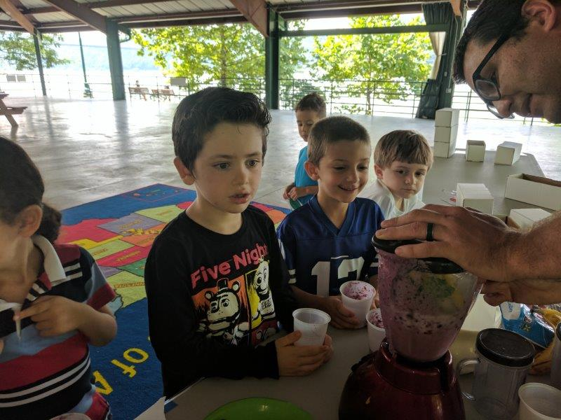 Children observing educator making smoothies at farmers market