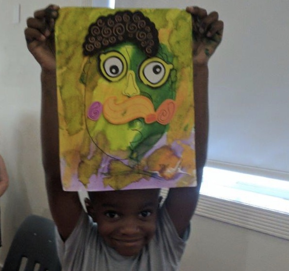 Joyful child displaying his artwork above his head