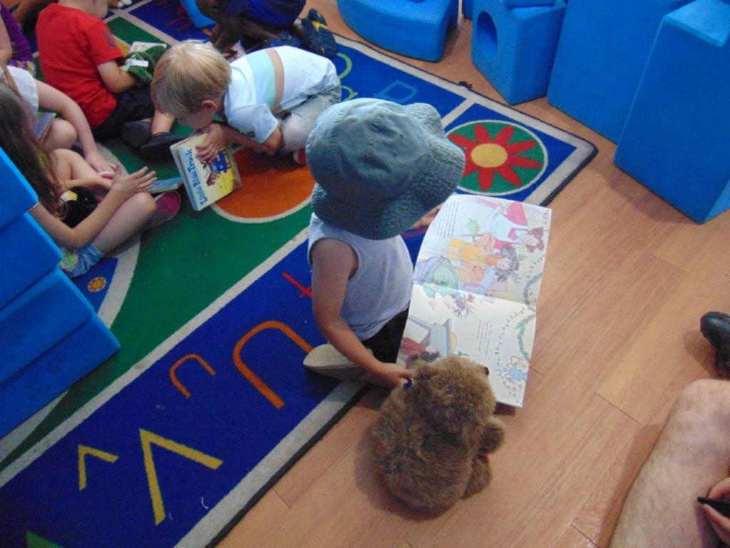 Preschool children reading books while sitting on a carpet