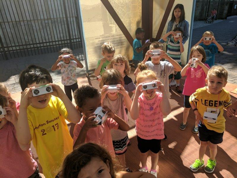 Children looking through binoculars during Science Camp