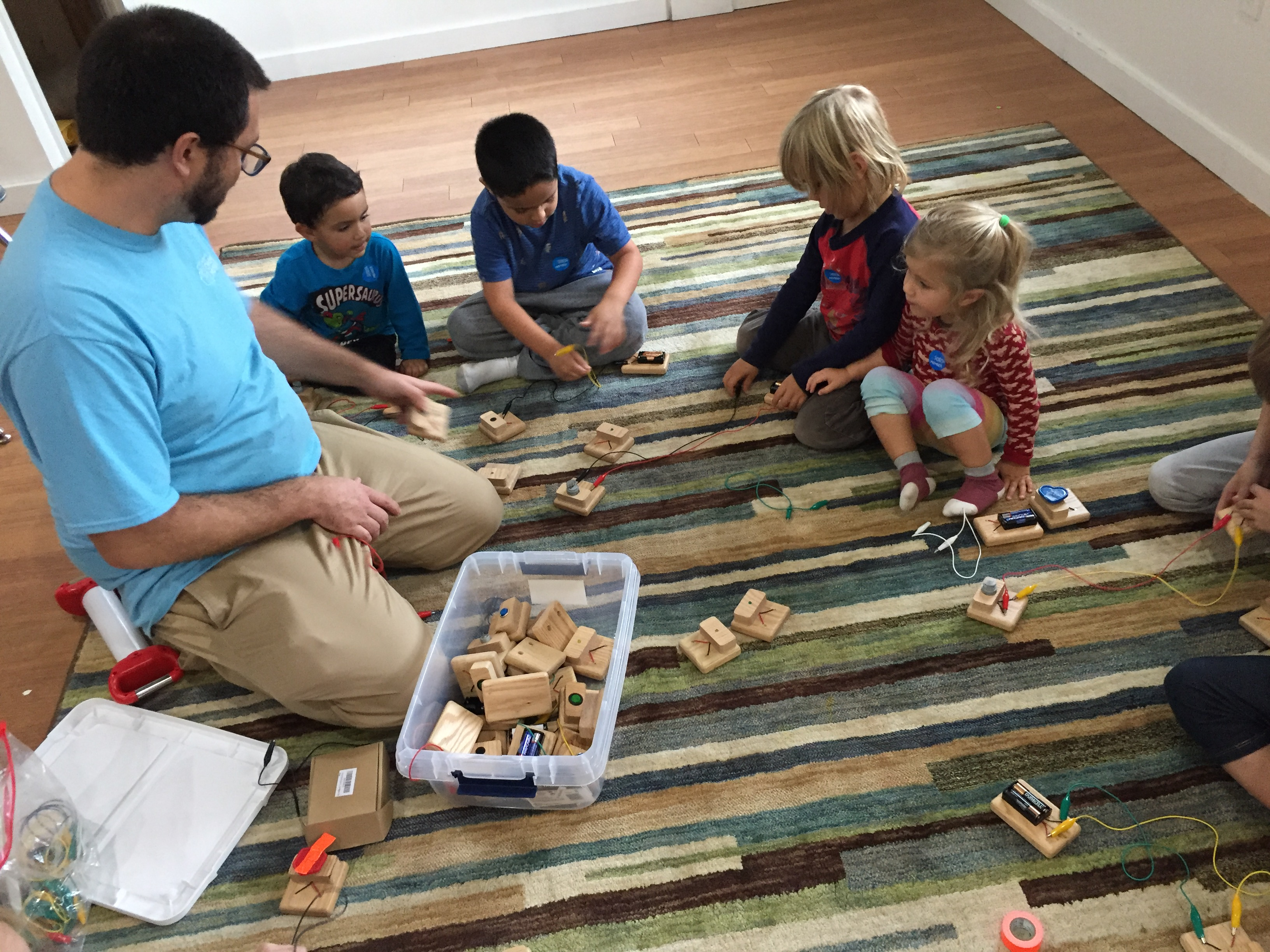 Children with educator exploring electric circuits while sitting on rug